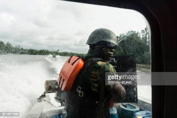 A member of NNS Pathfinder of the Nigerian Navy forces surveys his surroundings from the back of a gunboat patrolling in the creeks to look for...