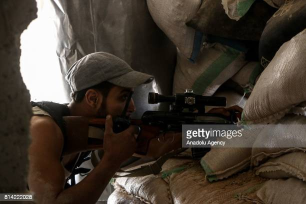 A member of opposition forces looks through a sniper rifle's scope during a clash after Assad Regime's forces hit a deconflict zone of opposition...