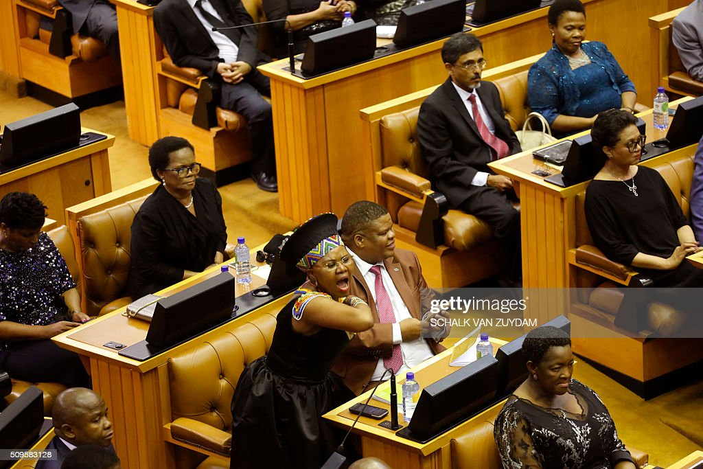 A member of parliament, center, shouts out against the Economic Freedom Fighters political party, disruption of South African President Jacob Zuma's state of the nation address in Cape Town, South Africa, on February 11, 2016. South Africa's radical leftist Economic Freedom Fighters (EFF) party walked out of President Jacob Zuma's state of the nation address after repeatedly interrupting his speech in chaotic parliamentary scenes. / AFP / AP / Schalk van Zuydam