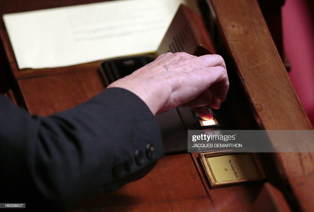 A member of Parliament votes during a debate on legalising same-sex marriage at the National Assembly on January 29, 2013 in Paris. France's parliament began examining draft legislation on same-sex marriage after months of rancorous debate and huge street protests by both supporters and opponents. AFP PHOTO / JACQUES DEMARTHON