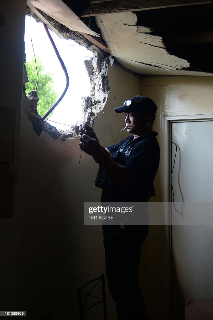 A member of police bomb disposal unit checks his equipment as he measures the diameter of the hole after a mortar shell believed to be from the Muslim rebels' position hit a residential house as government forces clash anew with remnants of Muslim rebels in Zamboanga City, on southern island of Mindanao on September 21, 2013. Philippine security forces killed eight Muslim rebels September 19, as they hunted the remnants of a guerrilla force hiding in homes of a major city and believed to be holding hostages.