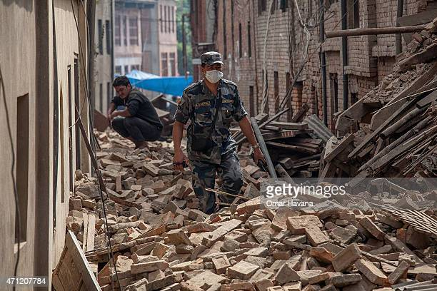 A member of police forces walk down a street covered in debris after buildings collapsed on April 26 2015 in Bhaktapur Nepal A major 78 earthquake...