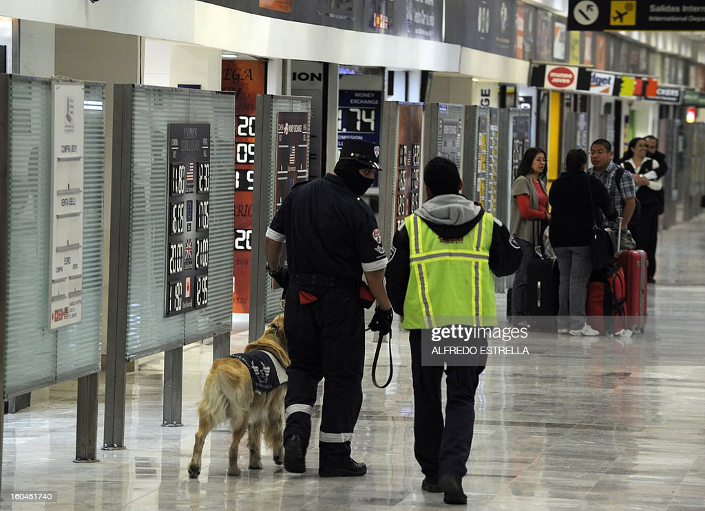 A member of private security with his dog searches for explosives at the T1 International Airport in Mexico City, on January 31, 2013. The death toll in the explosion at the headquarters of Mexico's oil giant Pemex rose to 25, the interior minister said. AFP PHOTO/