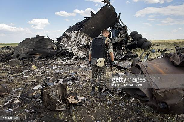 A member of proRussian separatist forces looks through the debris on the outskirts of Lugansk June 14 2014 of an IL76 transporter which was taken...