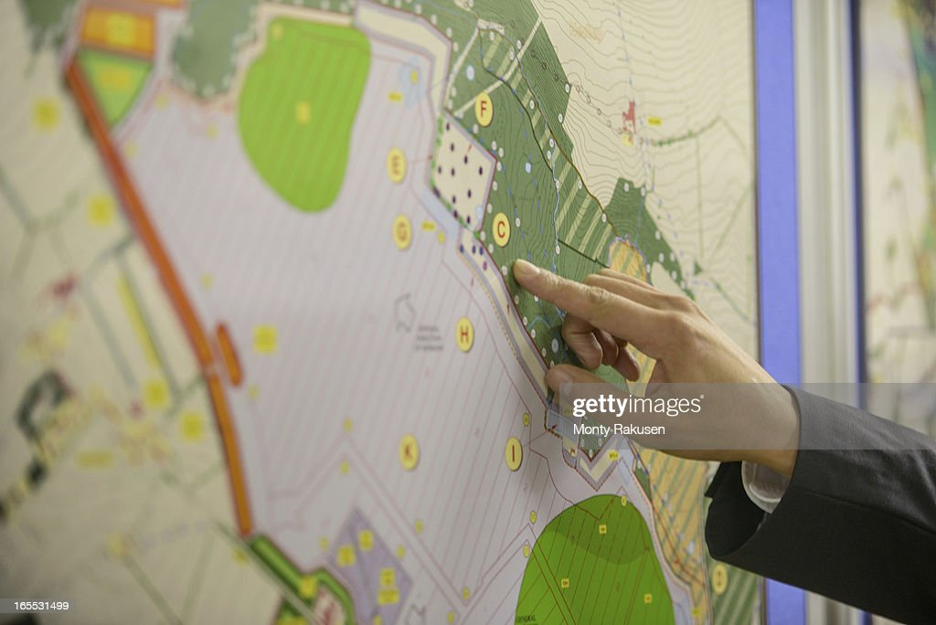 Member of public pointing at map of proposed planning inquiry in town hall