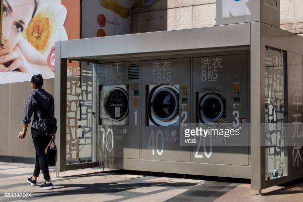 A member of public walks past shared washing machines and drying machines at a commercial plaza of Xuhui District on May 18 2017 in Shanghai China...