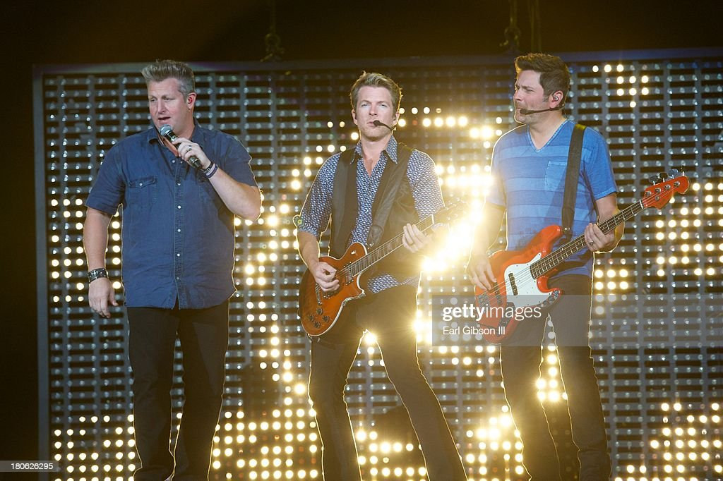 Member of Rascal Flatts (L-R) Gary LeVox, Jay DeMarcus Jr., and <a gi-track='captionPersonalityLinkClicked' href=/galleries/search?phrase=Joe+Don+Rooney&family=editorial&specificpeople=241526 ng-click='$event.stopPropagation()'>Joe Don Rooney</a> perform at Verizon Wireless Amphitheatre on September 14, 2013 in Laguna Hills, California.