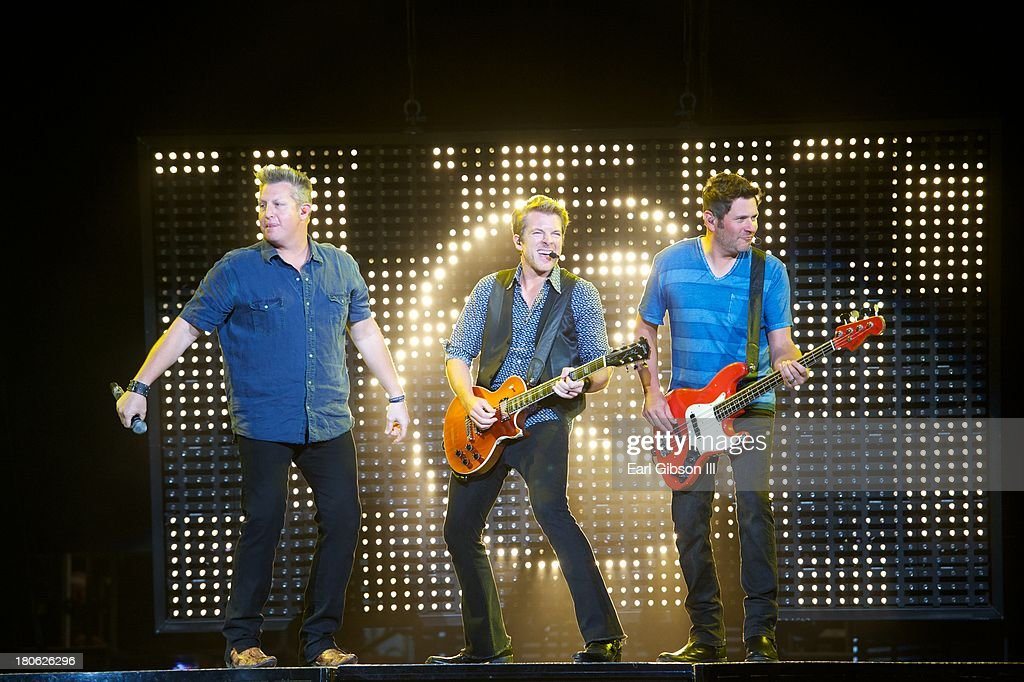 Member of Rascal Flatts (L-R) Gary LeVox, Jay DeMarcus Jr., and Joe Don Rooney perform at Verizon Wireless Amphitheatre on September 14, 2013 in Laguna Hills, California.