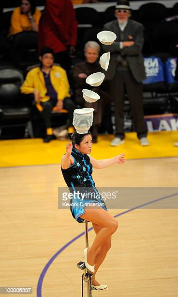 A member of Red Panda Acrobats rides a unicycle bicycle while performing during Game Two of the Western Conference Finals between the Los Angeles...