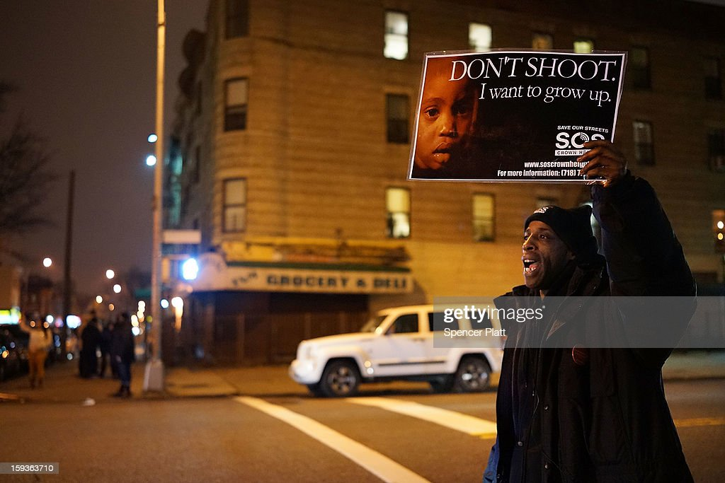 A member of Save Our Streets (S.O.S.) participates in a rally and vigil on the sidewalk near where a 16-year-old boy was shot last Tuesday evening, on January 12, 2013 in the Crown Heights neighborhood of the Brooklyn borough of New York City. The gathering was sponsored by the local group S.O.S., which is a community-based effort to end gun violence. S.O.S. holds the gatherings at all shooting locations in Crown Heights to draw attention to the violence and to encourage a community response to the shootings. While murders were down for 2012 in New York City, gun violence continues to plague many communities.