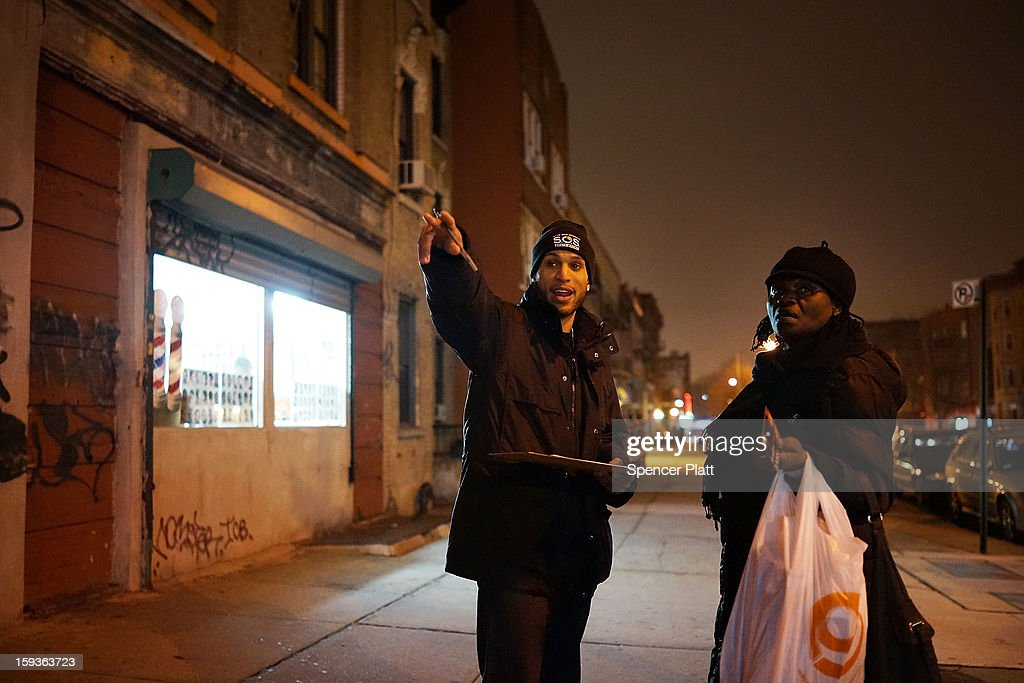 A member of Save Our Streets (S.O.S.) speaks to a resident near where a 16-year-old boy was shot last Tuesday evening, on January 12, 2013 in the Crown Heights neighborhood of the Brooklyn borough of New York City. The gathering was sponsored by the local group S.O.S., which is a community-based effort to end gun violence. S.O.S. holds the gatherings at all shooting locations in Crown Heights to draw attention to the violence and to encourage a community response to the shootings. While murders were down for 2012 in New York City, gun violence continues to plague many communities.