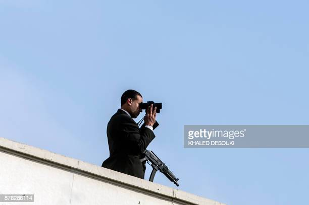 A member of security scans the surround area as he stands on the roof of the Arab League headquarters in the Egyptian capital Cairo on November 19...