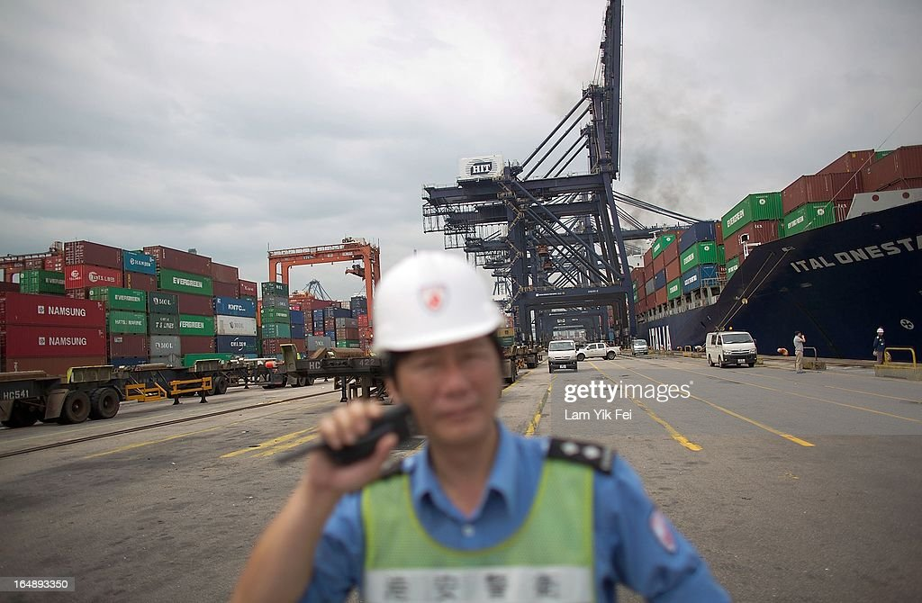 A member of security staff stands at the industrial action affected Kwai Chung Container Terminal on March 29, 2013 in Hong Kong, China. Over 100 workers, who are employed by Hongkong International Terminals, have taken strike action as they demand higher wages, claiming that that they have not received a pay raise in 15 years.