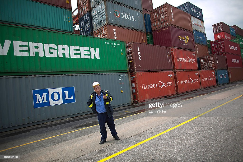 A member of security staff stands in front of stacked containers at the Kwai Chung Container Terminal on March 29, 2013 in Hong Kong, China. Over 100 workers, who are employed by Hongkong International Terminals, have taken strike action as they demand higher wages, claiming that that they have not received a pay raise in 15 years.