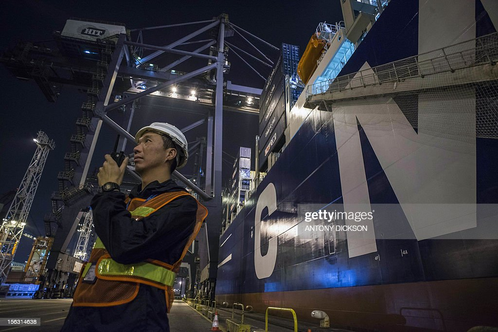 A member of security stands beside the CMA CGM Marco Polo container vessel at a container port in Hong Kong on November 13, 2012. The Marco Polo (16000 TEUS), on its maiden voyage, is CMA CGM's flagship and is the world's largest container vessel. AFP PHOTO / Antony DICKSON