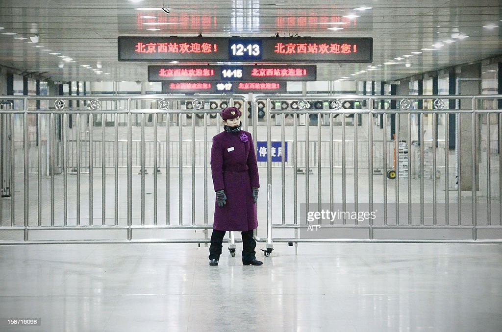 A member of security stands guard at a entrance of a platform for a high-speed train at the Beijing west railway station in Beijing on December 26, 2012. China on December 26 started service on the world's longest high-speed rail route, the latest milestone in the country's rapid and sometimes troubled super fast rail network. AFP PHOTO / WANG ZHAO