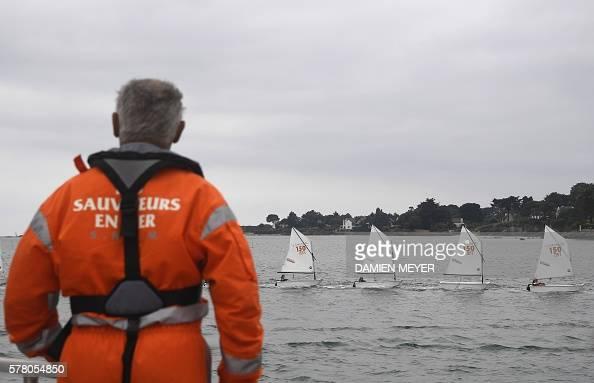 A member of SNSM looks at school boats sailing in the Gulf of Morbihan on July 20 2016 off the coast of La TrinitesurMer / AFP / DAMIEN MEYER