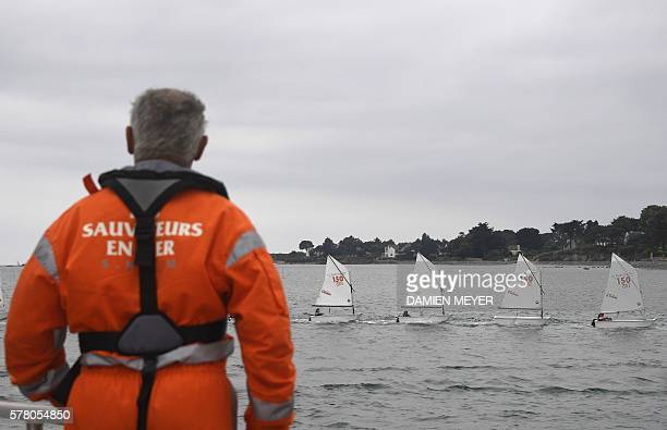 A member of SNSM looks at school boats sailing in the Gulf of Morbihan on July 20 2016 off the coast of La TrinitesurMer / AFP / DAMIEN MEYER