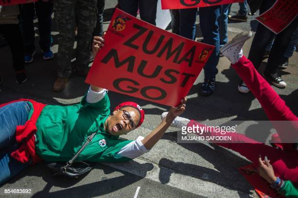 TOPSHOT A member of South Africa's main labour union federation COSATU waves a sign during a demonstration calling for the removal of South Africa's...