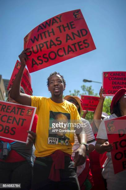 A member of South Africa's main labour union federation COSATU waves a sign during a demonstration calling for the removal of South Africa's...