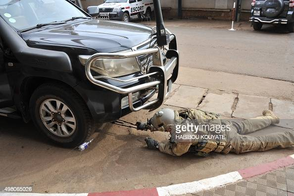A member of special forces checks under a car parked outside the Radisson Blu hotel in Bamako on November 20 after the assault of security forces...
