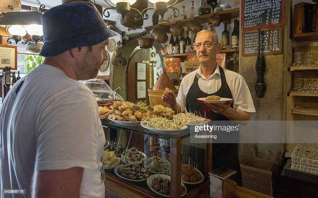 A member of staff at 'Ai Osti' bacaro serves cicchetti and wines to local customers on June 30, 2016 in Venice, Italy. The bacari which opens for lunch and dinner are the local down to earth version of a wine bars. Venetians stop to snack and enjoy 'ciccheti, a kind of Tapas traditionally washed down with a glass of wine.