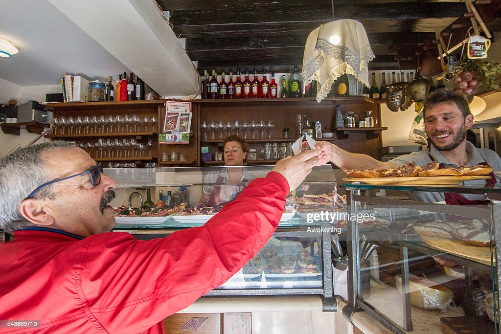 A member of staff at 'All' Arco' bacaro serves cicchetti and wines to local customers on June 30, 2016 in Venice, Italy. The bacari which opens for lunch and dinner are the local down to earth version of a wine bars. Venetians stop to snack and enjoy 'ciccheti, a kind of Tapas traditionally washed down with a glass of wine.