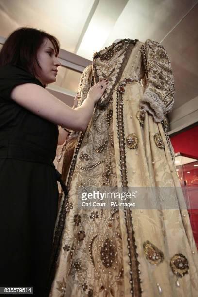 A member of staff at Bonhams Knightsbridge showroom adjusts the costume worn by Miranda Richardson in her role as Elizabeth I in Blackadder II at the...