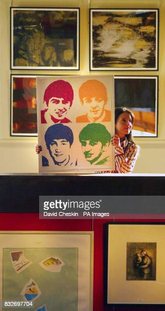 A member of staff at Lyon Turnbull Auctioneers in Edinburgh holds up a 2004 Peter Blake screenprint of the Beatles entitled 'Love Me Do'