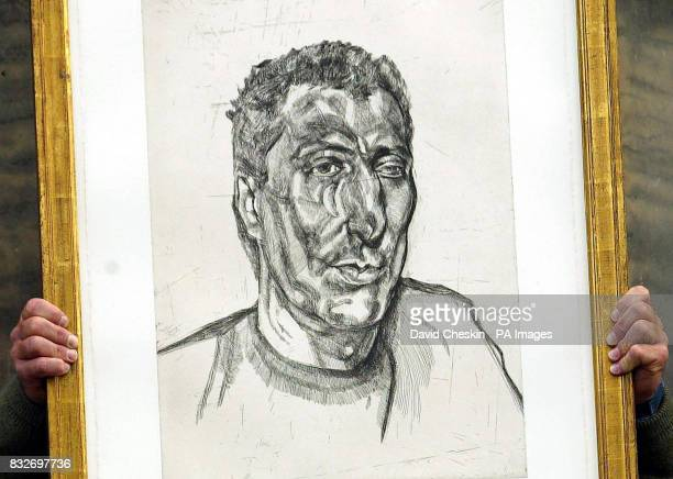 A member of staff at Lyon Turnbull Auctioneers in Edinburgh holds up a 1922 Lucian Freud print entitled 'The Head of Ali'
