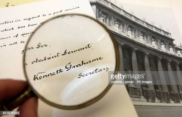 A member of staff at the Bank of England Museum examines a resignation letter written by author of 'The Wind in the Willows' Kenneth Grahame which...