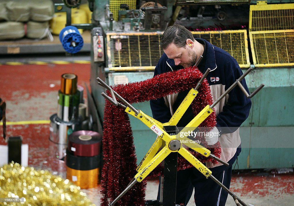 A member of staff at the Festive Productions Ltd factory, showroom, shop and warehouse makes lengths of tinsel on December 13, 2012 in Cwmbran, Wales. Although Christmas is less than two weeks away the staff at Festive are already planning and gearing up for Christmas 2013. The 14 acre fully integrated showroom, factory and warehouse measuring 250000 sq ft in size holds Festive Productions who are now the last manufacturer of tinsel in UK with the majority of tinsel sold in the UK also made at their factory in Wales. As well as tinsel, Festive, which is one of Europe's largest suppliers and manufacturer of Christmas and seasonal decorations, has increased its product portfolio, to include nearly every conceivable Christmas decoration category including baubles, tinsel garlands, wreaths, lights, fibre optic trees and artificial trees.