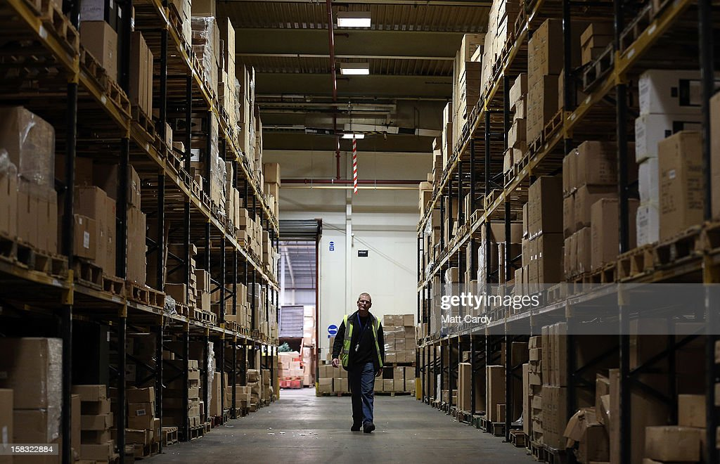 A member of staff at the Festive Productions Ltd factory, showroom, shop and warehouse looks for stock on the shelves in one of the warehouses on December 13, 2012 in Cwmbran, Wales. Although Christmas is less than two weeks away the staff at Festive are already planning and gearing up for Christmas 2013. The 14 acre fully integrated showroom, factory and warehouse measuring 250000 sq ft in size holds Festive Productions who are now the last manufacturer of tinsel in UK with the majority of tinsel sold in the UK also made at their factory in Wales. As well as tinsel, Festive, which is one of Europe's largest suppliers and manufacturer of Christmas and seasonal decorations, has increased its product portfolio, to include nearly every conceivable Christmas decoration category including baubles, tinsel garlands, wreaths, lights, fibre optic trees and artificial trees.