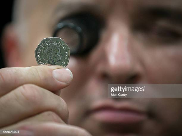 A member of staff at the Royal Mint inspects a new 50p coin that has been produced on August 1 2014 in Llantrisant Wales The Royal Mint formed over...