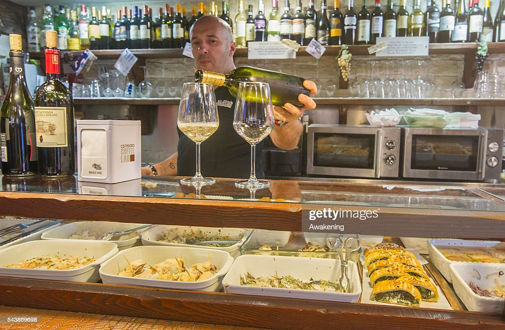 A member of staff at 'Un Mondo Divino' bacaro serves cicchetti and wines to local customers on June 30, 2016 in Venice, Italy. The bacari which opens for lunch and dinner are the local down to earth version of a wine bars. Venetians stop to snack and enjoy 'ciccheti, a kind of Tapas traditionally washed down with a glass of wine.
