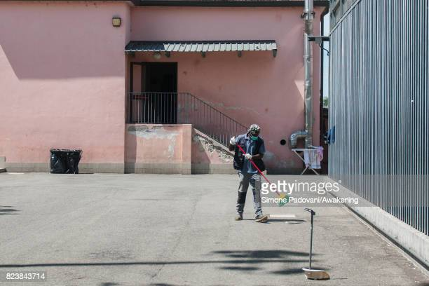A member of staff cleans a courtyard of the CARA Hub asylum seekers centre on July 27 2017 in Bologna Italy In an effort to address the overcrowding...