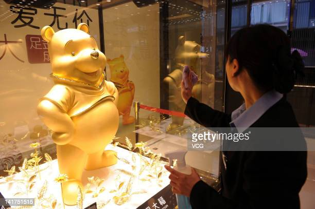 A member of staff cleans the glass cabinet displaying a gold figure of Winnie The Pooh at a jewellery store on March 22 2012 in Chengdu China The 110...