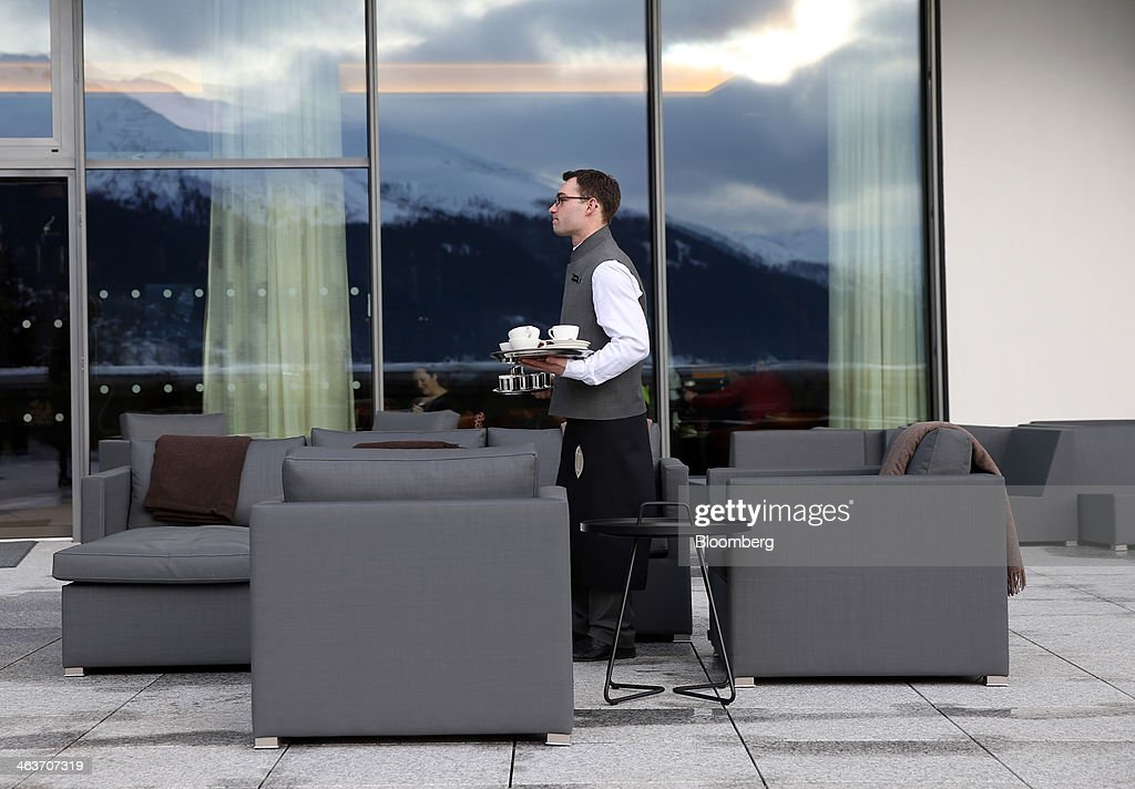 A member of staff clears away empty crockery from a table on the outside terrace at the InterContinental hotel Davos, operated by InterContinental Hotels Group Plc (IHG) in Davos, Switzerland, on Saturday, Jan. 18, 2014. Next week the business elite will gather in the Swiss Alps for the 44th annual meeting of the World Economic Forum (WEF) in Davos for the five day event which runs from Jan. 22-25. Photographer: Simon Dawson/Bloomberg via Getty Images