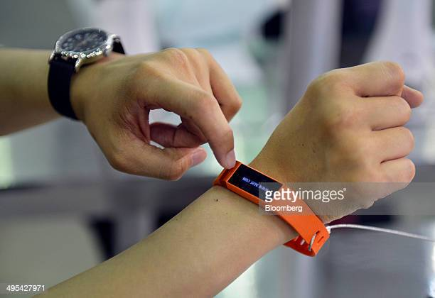 A member of staff demonstrates the Acer Liquid Leaf smart watch on display at the Acer Inc booth during the Computex Taipei 2014 expo at the Taipei...