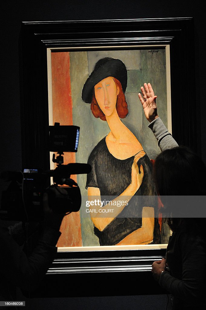 A member of staff discusses a work entitled ''Jeanne Hebuterne (au chapeau)' by Italian artist Amedeo Modigliani at Christies auction house in central London on February 1, 2013. Due to form part of the Impressionist and Modern Art Evening Sale on February 6, it is expected to fetch between 16-22 million GBP (25-33 million USD - 18-25 million EUR).