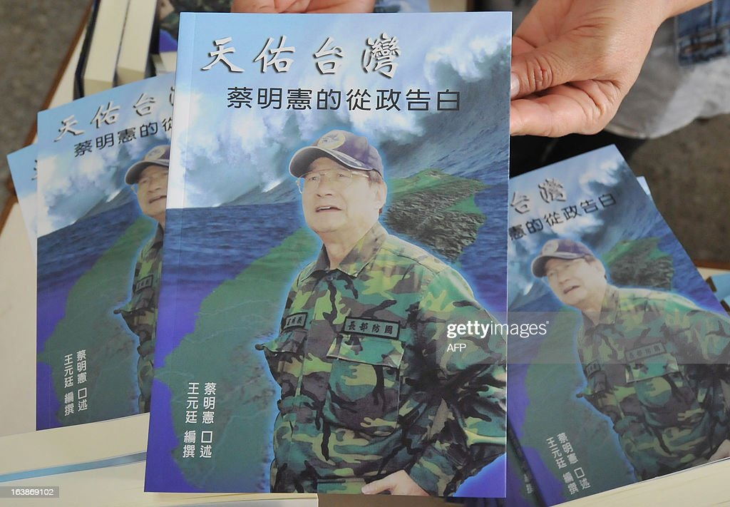 A member of staff holds a book entitled 'God bless Taiwan' by Michael Tsai, a politician turned defence minister in the former government of the China-sceptic Democratic Progressive Party (DPP), during a press conference in Taipei on March 17, 2013. Taiwan has developed its first medium-range guided missile that could be used against former rival China, according to a former defence minister in a new book cited by a media report on March 17. AFP PHOTO / Mandy CHENG