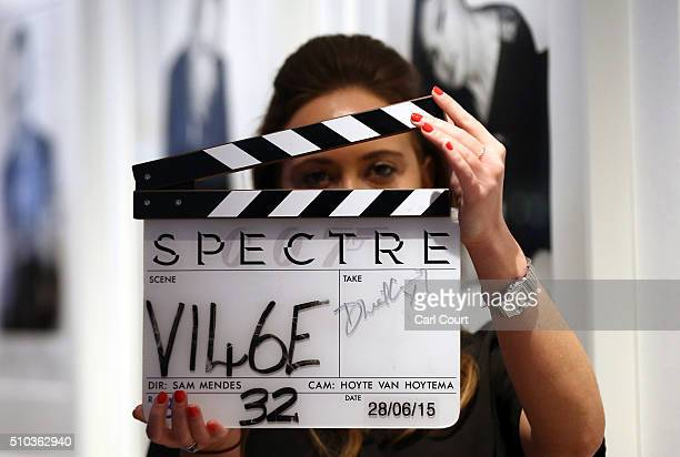 A member of staff holds a clapper board signed by Daniel Craig and used in the Bond film Spectre during a photocall at Christie's auction house on...
