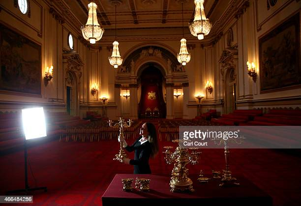 A member of staff holds a silvergilt candelabra one of a pair during a photocall to showcase items from the Royal Collection used during state...