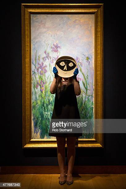 A member of staff holds 'Tete au masque' a ceramic plate by Pablo Picasso estimated between £60008000 in front of Claude Monet's 19141917 piece 'Iris...