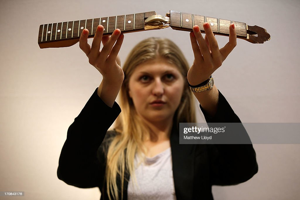 A member of staff holds the smashed neck of Kurt Cobain's guitar, for sale at Christie's South Kensington on June 19, 2013 in London, England. The item is part of an auction entitled 'Pop Culture' featuring memorabilia charting the history of cinema, pop and rock and roll.