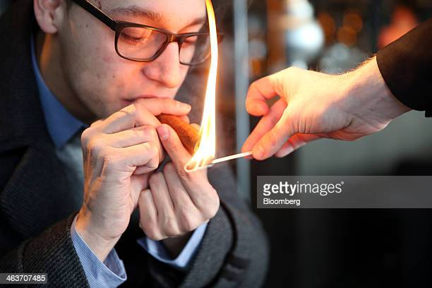A member of staff lights a cigar for a guest as he sits in the 'Studio Grigio' bar at the InterContinental hotel Davos operated by InterContinental...