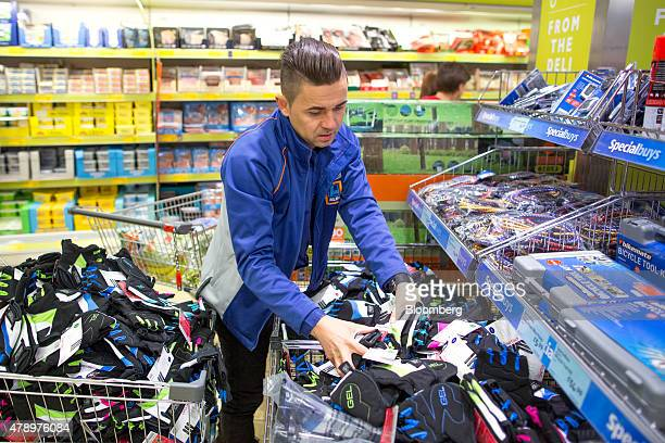 A member of staff loads a sales bin with fingerless gloves inside an Aldi supermarket store in London UK on Monday June 29 2015 The growth of Aldi...