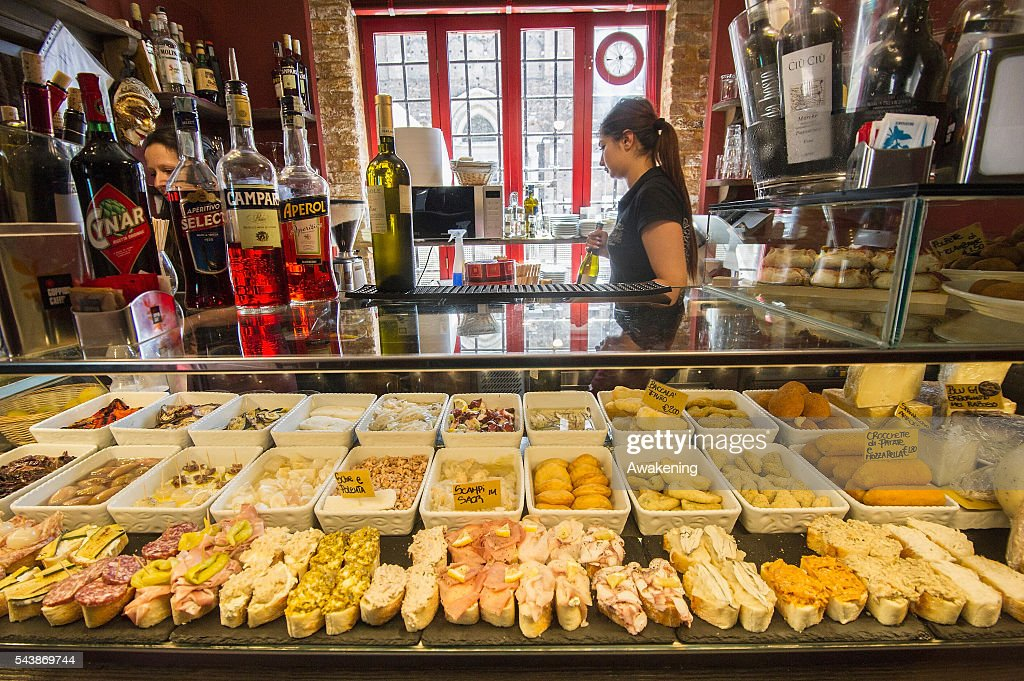 A member of staff of the 'Al Ponte' bacaro arranges a display of cicchetti on June 30, 2016 in Venice, Italy. The bacari which opens for lunch and dinner are the local down to earth version of a wine bars. Venetians stop to snack and enjoy 'ciccheti, a kind of Tapas traditionally washed down with a glass of wine.