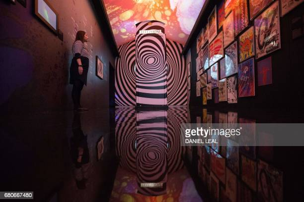 A member of staff poses at the 'Down the rabbit hole' room featuring a telephone cabin which was inspired by the famous psychedelic UFO club in...