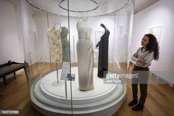 A member of staff poses beside a 1992 Catherine Walker grey silk satin dress with simulated pearl embroidery on the bodice worn by Princess Diana for...